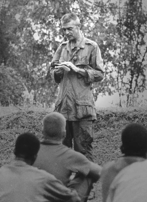 Conducting a prayer service in the field. / Father Capodanno Guild.