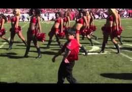 Kid dances with cheerleaders