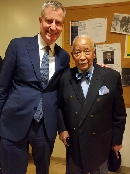 [Mayor Bill de Blasio, MIA '87, poses for a photo with former NYC Mayor David Dinkins. de Blasio is in a dark blue suit and white shirt, and Dinkins is in a dark jacket with a striped blue bow tie.]