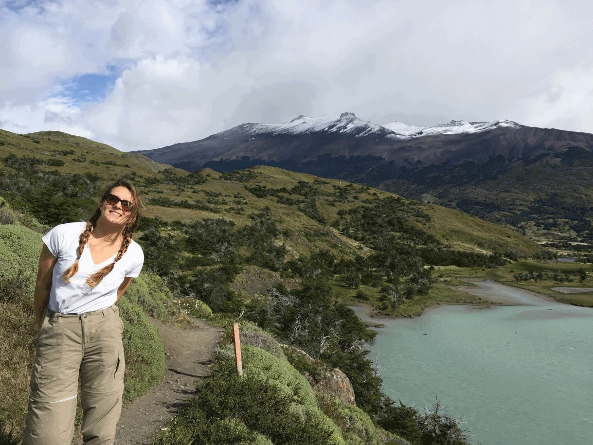 Sierra standing on a large grass hill in Patagonia, Chile while on a hike.