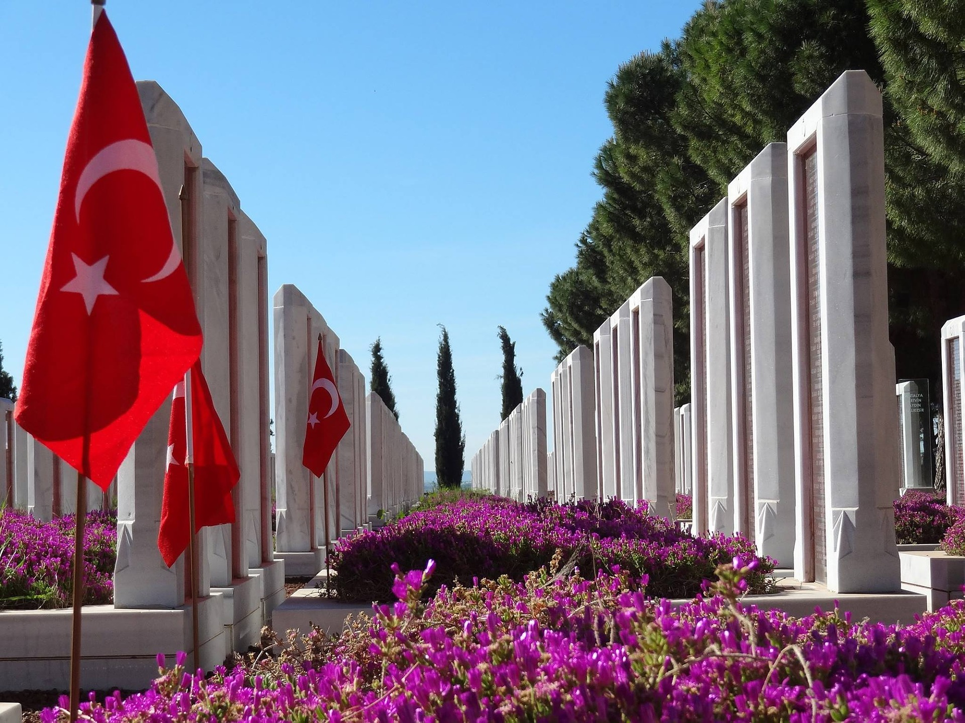 A flag of Turkey on a stand outside surrounded by pink flowers in a courtyard