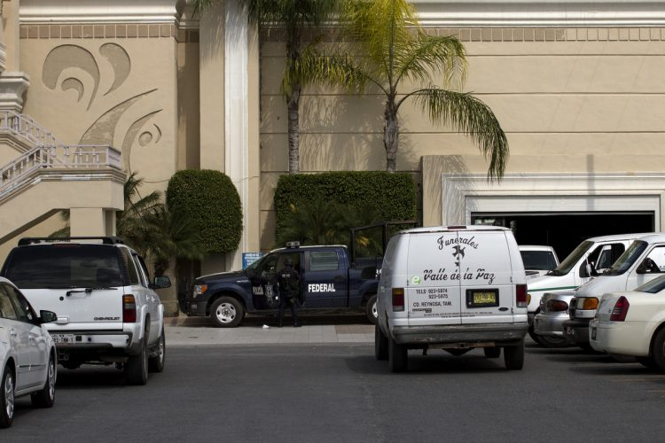 Federal Police, guards a funeral home  in Reynosa, where some of 72 bodies of men and women that were allegedly killed by the Zetas drug gang, are kept in Reynosa , Mexico, Aug. 27, 2010. A wounded migrant who escaped the Zetas gang stumbled into a military checkpoint and led marines to the scene were migrants from Brazil, Ecuador, El Salvador and Honduras were executed. (Guillermo Arias)