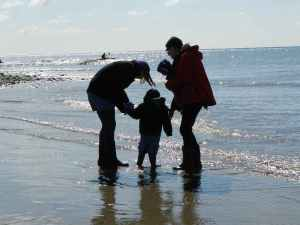 two adults and a child at the sea edge