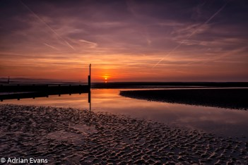 Seascape Sunset, aircraft vapor trails North Wales UK. Contrails or vapor trails are long, thin artificial clouds that sometimes form behind aircraft