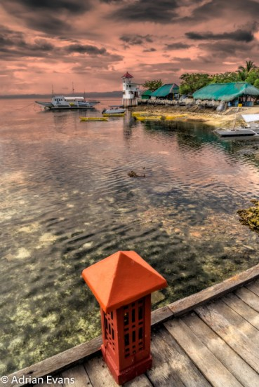 Tour boats moored off the Nalusuan Island Philippines at sunset