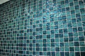 Pastilha de vidro em alto relevo em 02 tons de azul translúcido, refletido em espelho em um banheiro. Foto e obra: Adriano Gronard