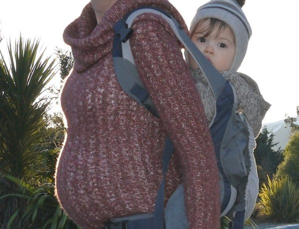 pregnant mother babywearing a toddler in an ergobaby carrier