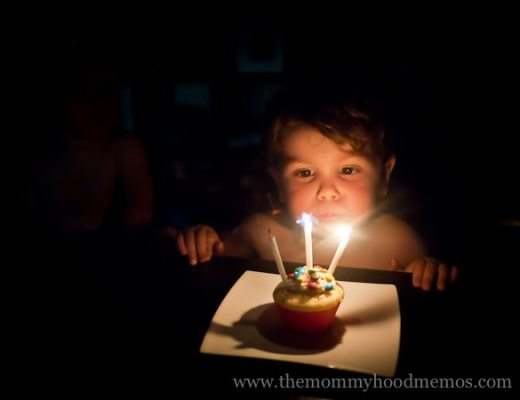 three year old blowing out candles