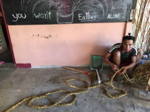 Restaurant owner making decorations from rice straw