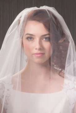 Bride wearing a blusher style veil.