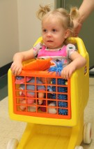 MacKenzie plays in a toy shopping cart at the Huntsville CRS office