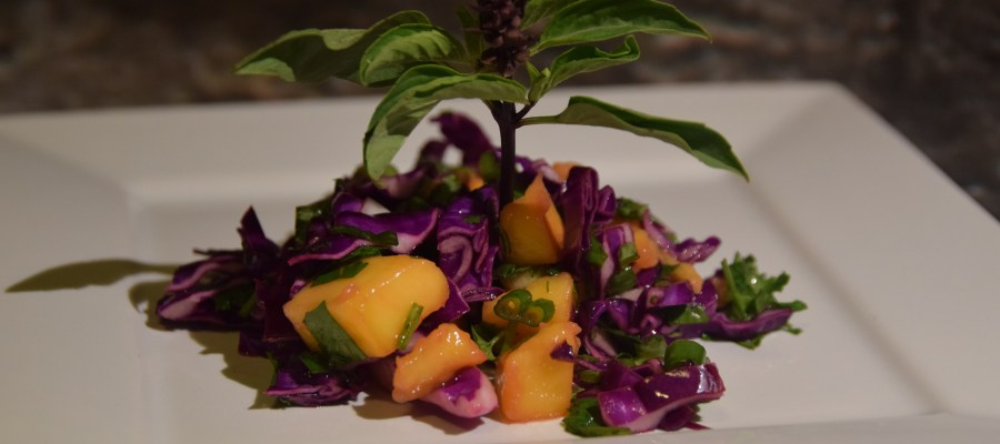"Orange mango, purple and green Thai basil, purple cabbage, and other green herbs in a slaw on a white plate, with a ""tree"" sprig of Thai basil in the center."