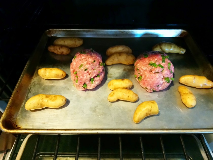 Image shows a silver sheet tray pan in the oven, with two uncooked meatloaves surrounded by yellow fingerling potatoes.