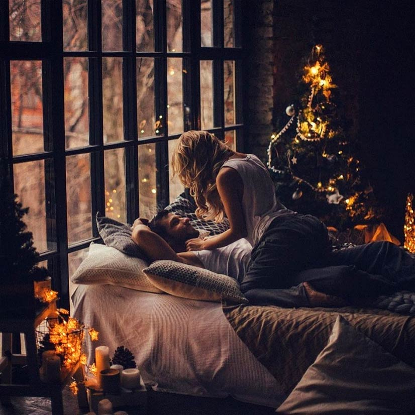 Couple kissing on bed at Christmas