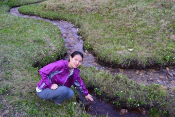 Wang dips her hands into a stream on a ranch near Taos, New Mexico, in July 2013. Her research focuses on environmental and natural resource economics, with an emphasis on water quality and water resources management.