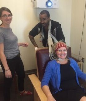 Witkiewitz, seated, is pilot testing EEG tasks in the Logan Hall Psychology Clinical Neuroscience Center in August 2016 with her graduate students, Sam Robinson and Elena Stein. Witkiewitz's recent research focuses on the development of a novel behavioral intervention that combines neuromodulation with mindfulness meditation to reduce heavy drinking. Photo by Stevi Gallegos.