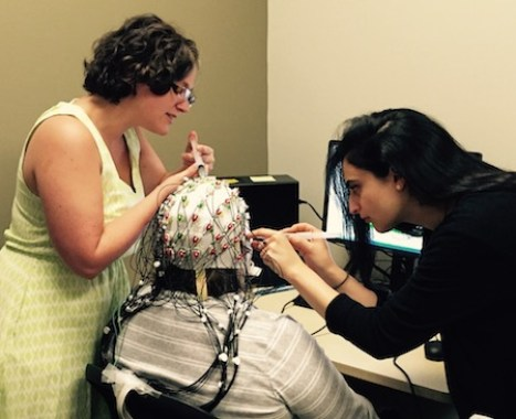 Dr. Jessica Richardson, center, an assistant professor and speech-language pathologist in the Department of Speech and Hearing Sciences at The University of New Mexico, helps students Sarah Grace Dalton, left and Sheida Abdi, right to troubleshoot EEG paradigms in summer 2016. Richardson who also works with the Center for Brain Recovery and Repair, focuses her research on recovery from acquired brain injury, with a specific focus on aphasia recovery, neural plasticity, and treatment approaches, including brain stimulation, that improve life participation.