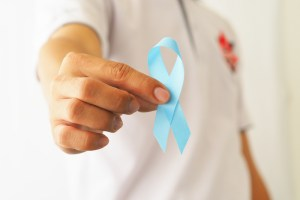 male hand holding blue prostate cancer awareness ribbon.