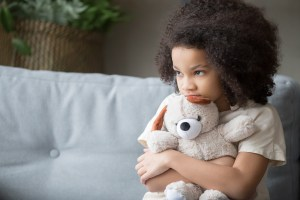 Upset girl holding teddy bear and looking away.