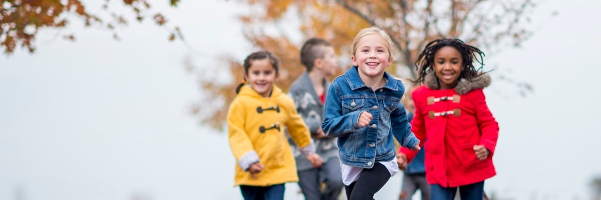 Children running through leaves
