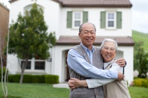 Happy Chinese Elderly Couple Standing in front Yard