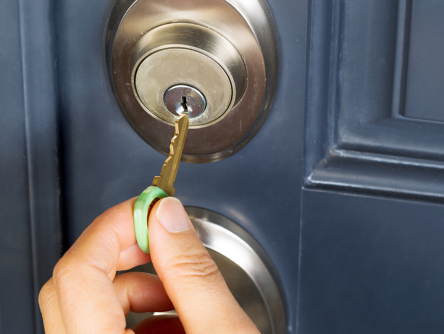 A hand putting house key into front door lock of house