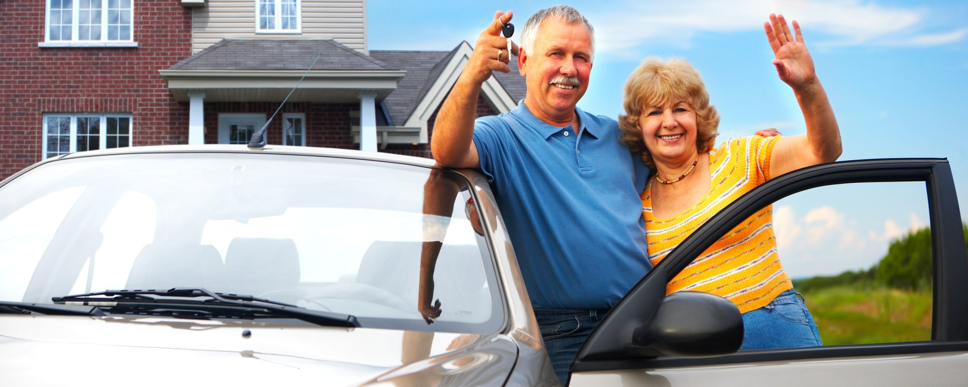 Husband and wife standing in front of a house, smiling next to their new car with the driver door open.