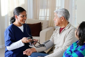 Caregiver taking a senior's blood pressure.