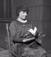 Helen Keller sitting holding a magnolia flower