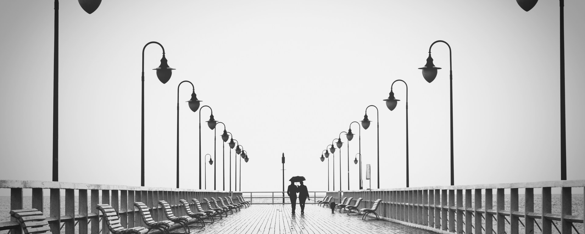 Two people walking on a pier in the rain.