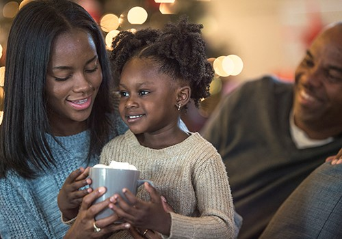 A family sits together on a couch. The mother helps her daughter hold a mug of hot chocolate.