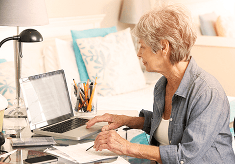 A woman looks at documents while sitting at her laptop.