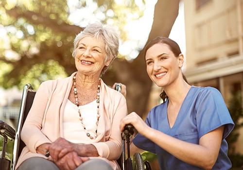 A woman wearing scrubs kneels next to a woman sitting in a wheelchair.