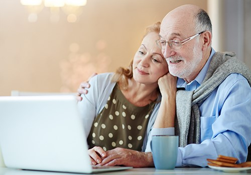 A senior couple smiles while looking at a laptop.