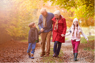 Grandparents walk in the woods with two grandchildren in the fall.