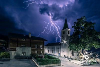 Bliksemschicht in wit kerkje in Unterbäch in Wallis Zwitserland. Uitgeworpen door een blauw paarse wolk in de vorm van een draak.