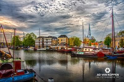 Landschapsfoto van boten in de Museumhaven in Gouda met op de achtergrond mooie gevels en de Kerk.