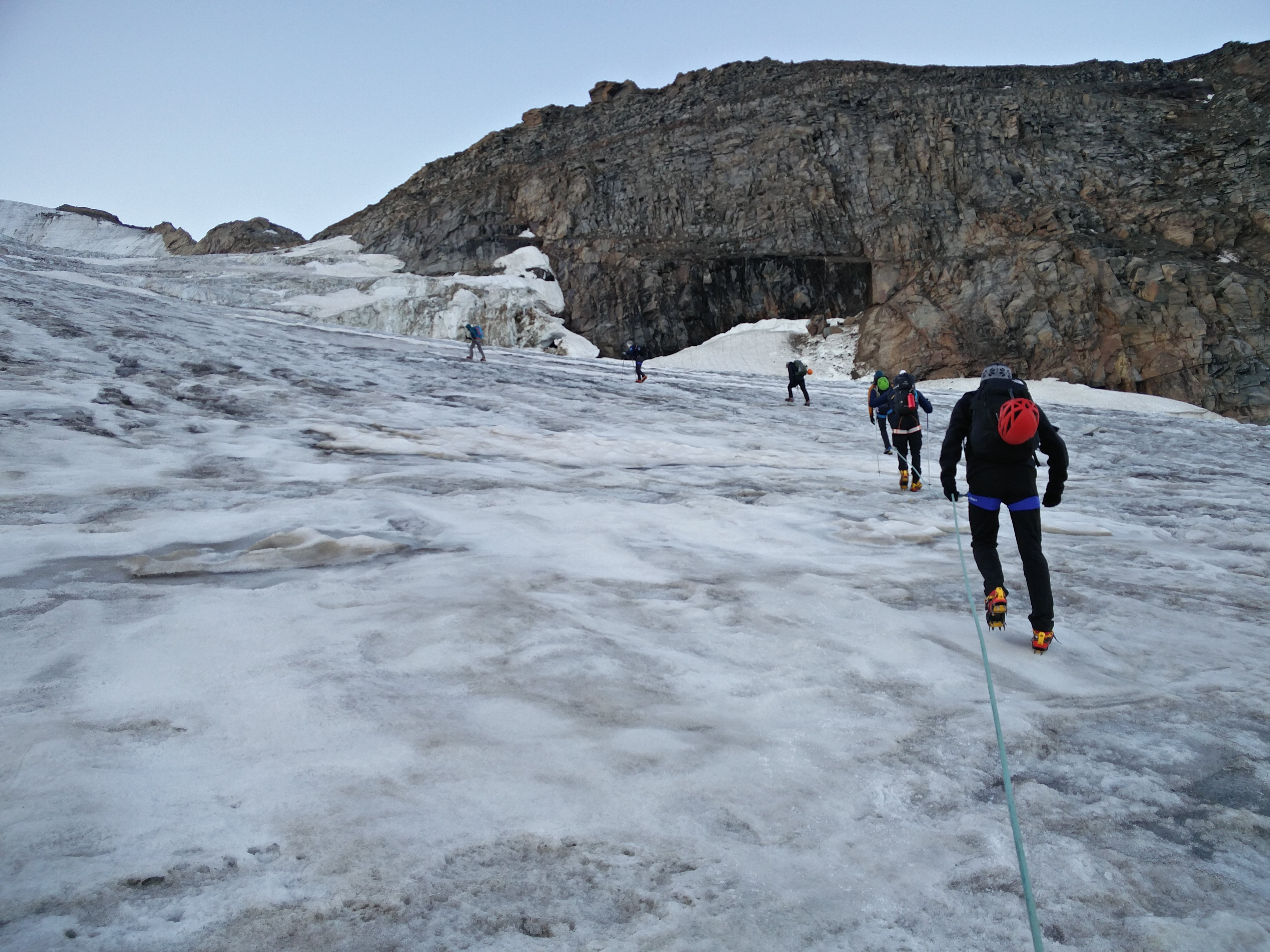 Making our way up on a glacier. Roped up already in crampons and with ice axes ready to action. We are properly on Climb Gran Paradiso acclimatisation day.