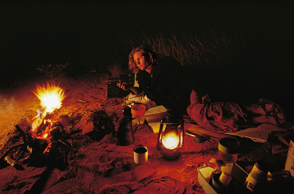 Robyn Davidson by the fire along her solo trek across the Australian desert. Photography by Rick Smolan/Against All Odds Production