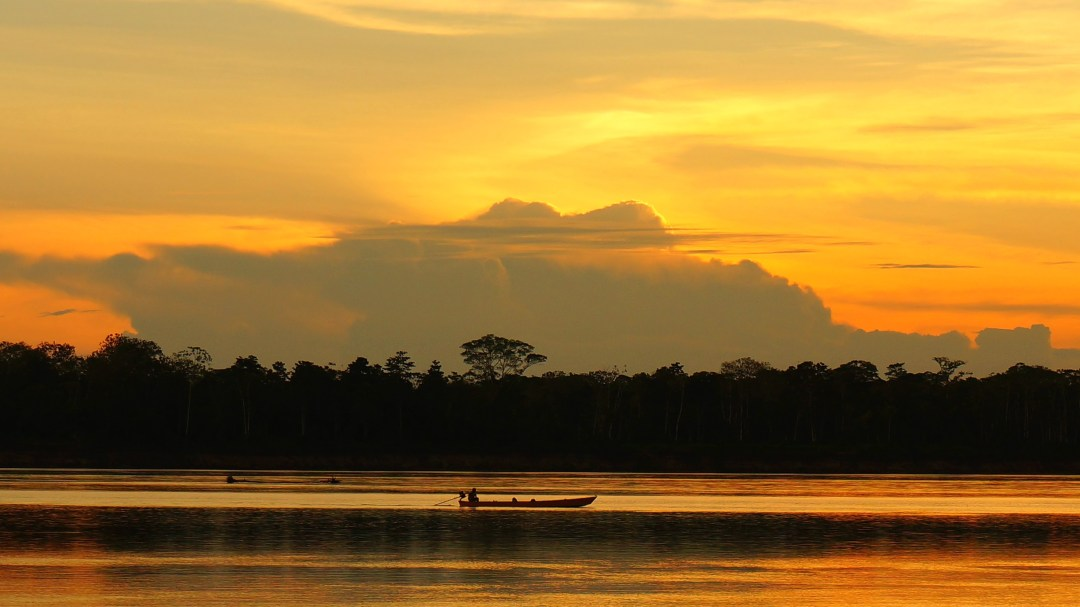 Another beautiful Amazon sunset. Our trail guide Tyo is driving our boat to come meet us.