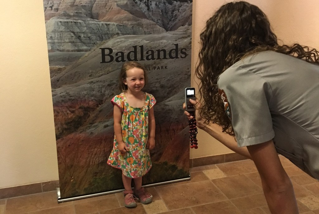 Jane getting her photo taken by a ranger for the fossil finders wall in the visitors center.