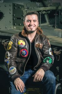 George Retelas, director, poses next to a plane.