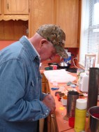 Dad fixing up the wick for his candle and plugging the hole at the bottom with clay.