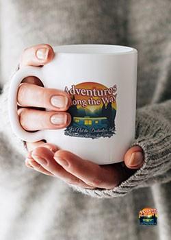 Woman holding coffee mug with adventures along the way logo