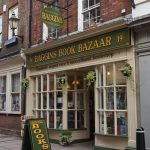 """A bookstore with a overhead sign that reads """"Baggins Book Bazaar."""""""