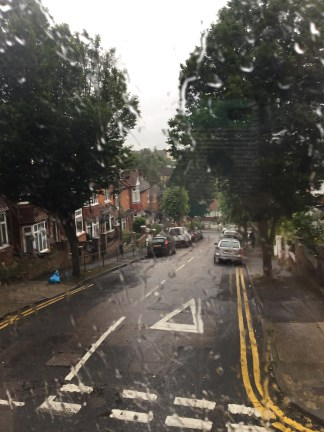 The view from a car with a rain-soaked window looking out to a residential street.