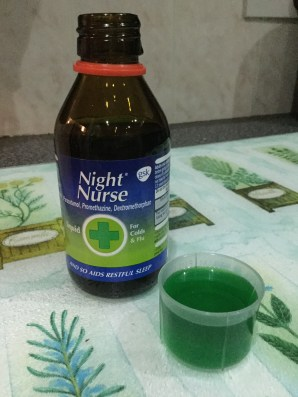 A bottle of NiteNurse with a cap full of the green medicine.