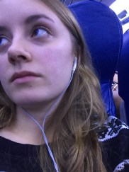 A tired girl sitting on an airplane waiting to disembark.