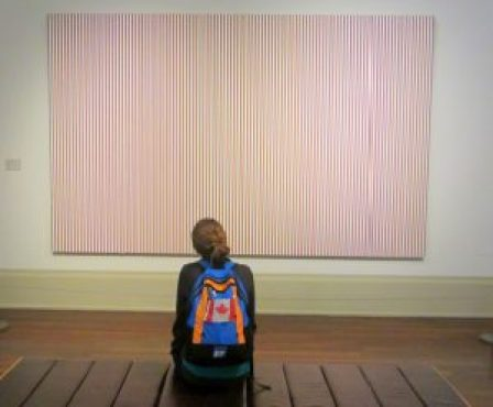 A girl with a backpack on looks at a large striped art piece hanging on the wall of a gallery.