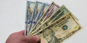 $10, $20, $50, $100 bills in hand